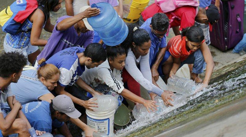 Les habitants de Caracas récupèrent l'eau qui fuit d'une canalisation de la rivière Guaire, l'une des plus polluées du pays.