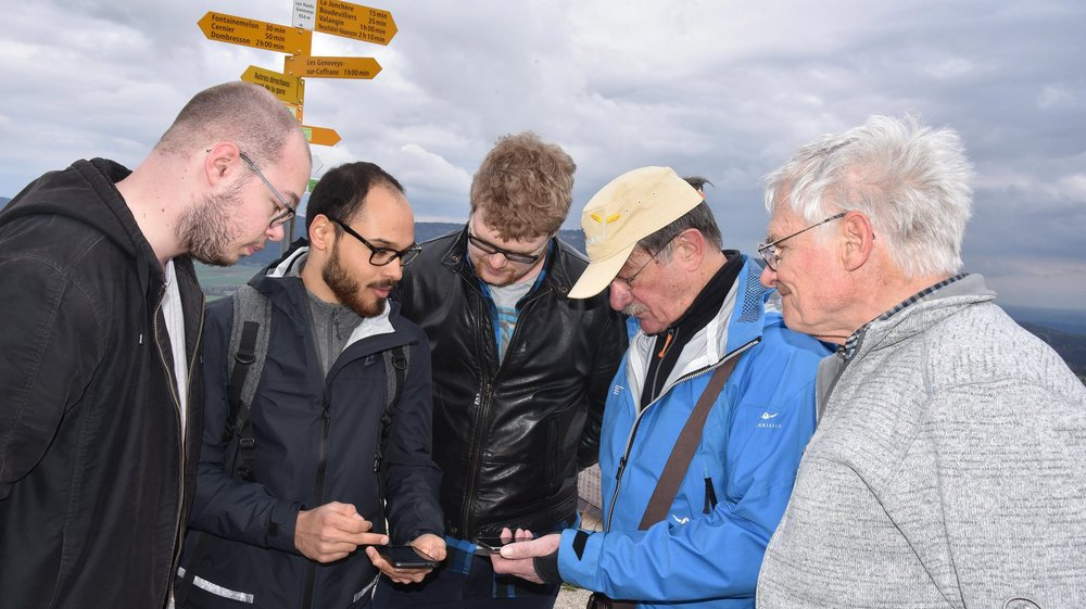 Jules Perrelet, Axel Rieben et Jérémy Dubois (à gauche), concepteur ou optimisateurs de l'application pour la HE-Arc ingénierie, présentent Hikoo à Henri Cosandey (en bleu) et Léonard Farron, respectivement président et responsable des sentiers de Neuchâtel Rando.