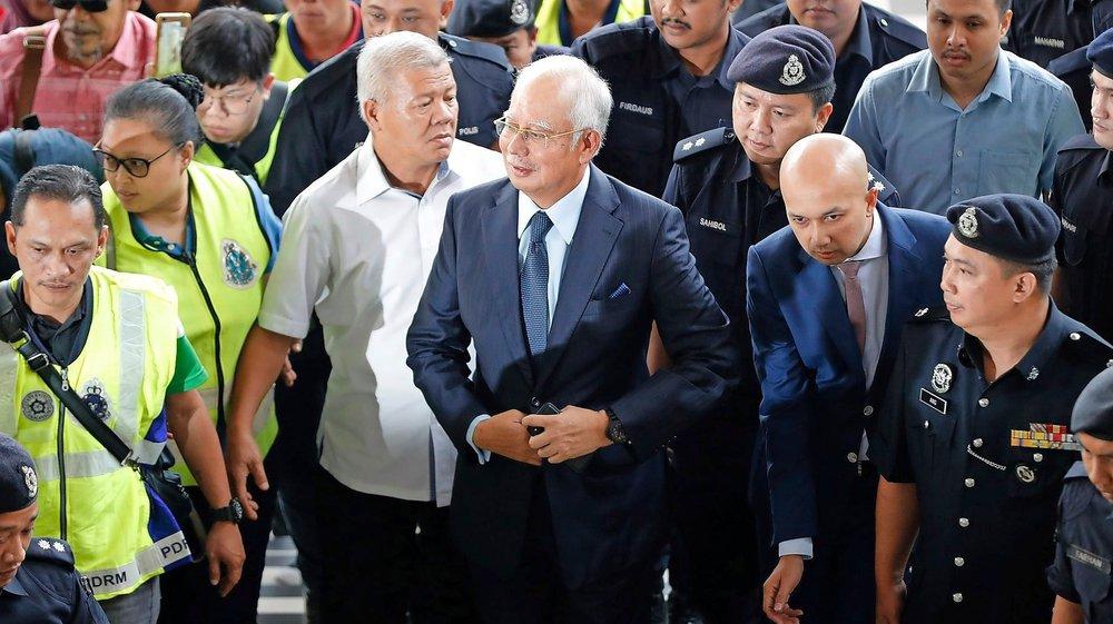 Accusé de s'être enrichi personnellement aux dépens du fonds souverain 1MDB, l'ancien premier ministre malaisien Najib Razak (au centre)  s'est présenté, mi-février, pour son procès à Kuala Lumpur.