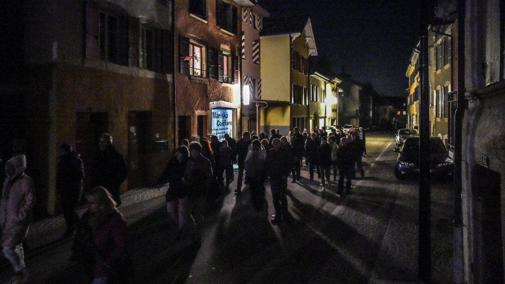 Dans la Grand'Rue de Corcelles, l'éclairage public était éteint samedi soir. Restaient les enseignes lumineuses des commerces et les fenêtres des logements.