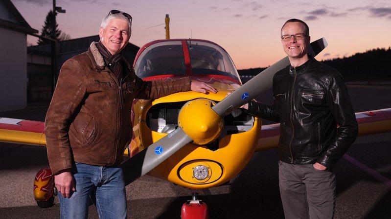 Jean-François Iseli (à gauche) et Yves Joly posent devant l'avion-école de l'Aéro-club des Montagnes neuchâteloises, le Piper Cherokee avec lequel ils ont volé en 2016 jusqu'à Dakar.