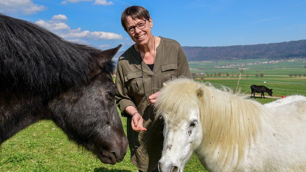 Après une journée de travail, Anne Challandes aime se ressourcer auprès de ses poneys, Melchior (noir) et Flocon (blanc), et de son âne Jules qui pâture au loin.