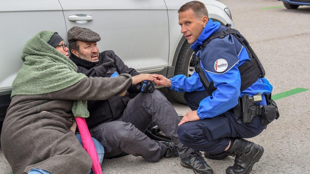 Un policier s'accroupit et tente de rassurer un couple effrayé. Ce scénario catastrophique joué samedi au parking de l'usine ValFleurier à Buttes n'est qu'une simulation. Photo: Christian Galley