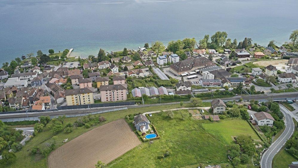 """Au premier plan, le secteur """"Au Roncinier"""" où devrait s'élever une septantaine d'appartements. Derrière, Chez-le-Bart et le lac de Neuchâtel."""