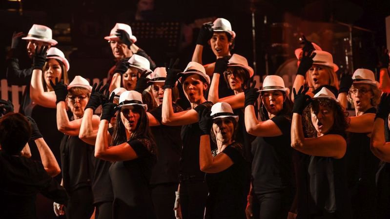 """La chorale locloise Free'son, chapeaux en mains, pour une version revisitée du thème musical du film """"Borsalino""""."""