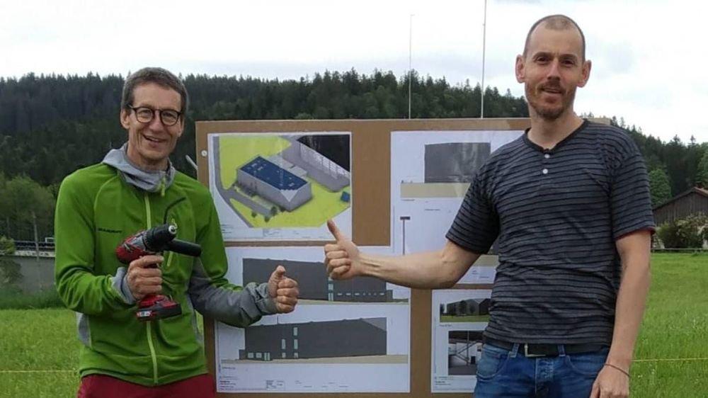 Jean Chèvre et Camille Guignard, les deux initiateurs du projet de salle d'escalade au Locle, devant le panneau de présentation du projet à côté des gabarits qui viennent d'être posés.