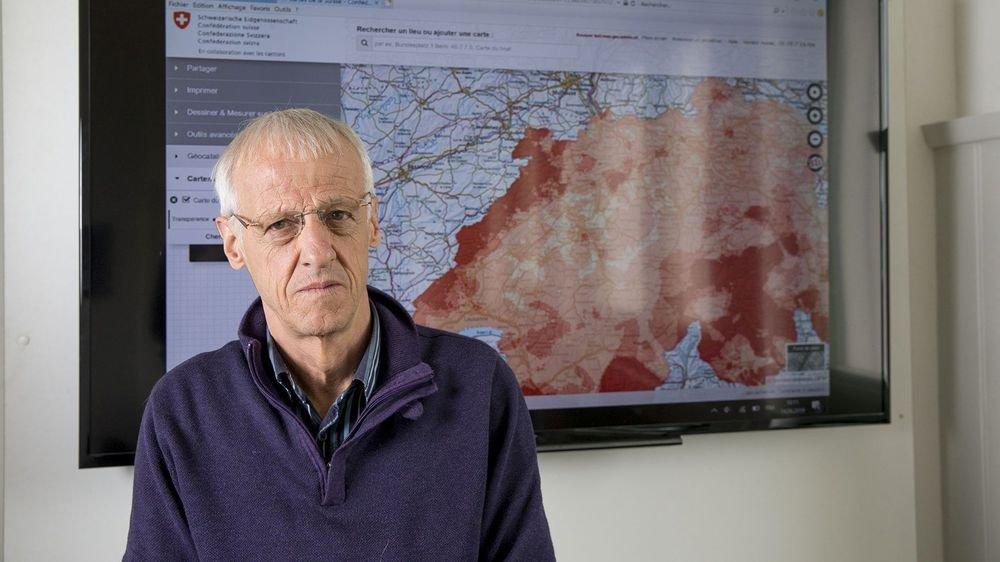 Pierre Renaud, ingénieur-conseils en énergie et environnement au bureau Planair de La Sagne, devant une carte de la Suisse, où les régions les plus touchées par le radon sont en rouge vif.