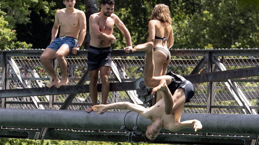 A Berne, des jeunes se rafraîchissent en sautant dans l'Aar depuis un pont.