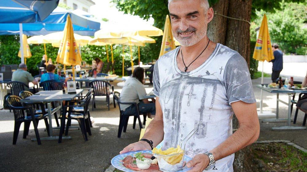 José Saiz présente son menu à l'ombre de l'un des arbres de la terrasse.