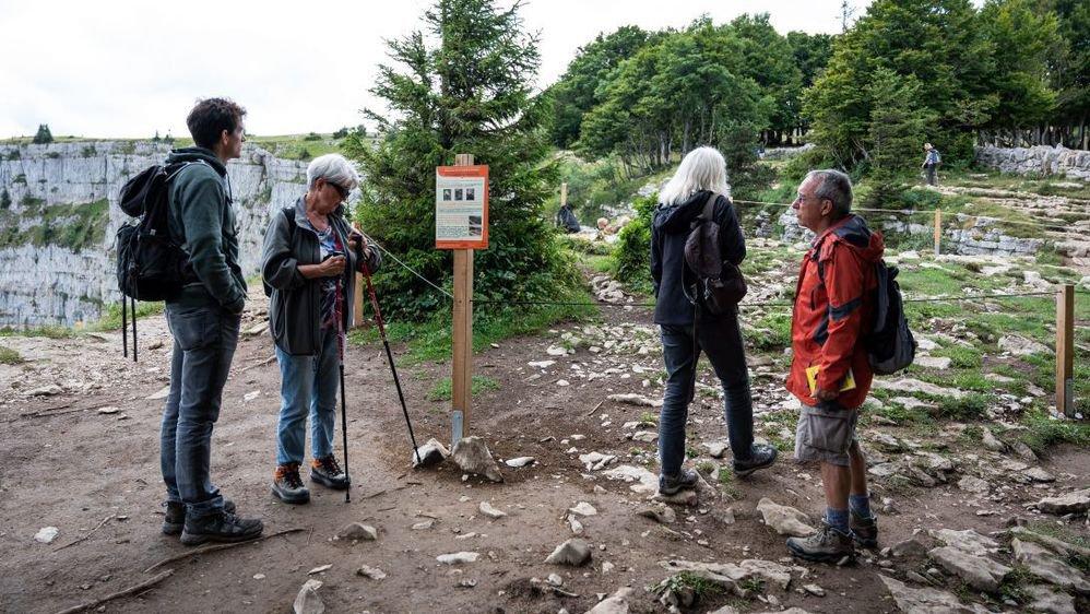 Des touristes au Creux-du-Van, devant un enclos de renaturation tout proche du point de vue dit du pharmacien.