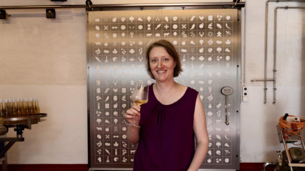 L'œnologue devant la cave du château, modifiée une dernière fois en 2014. Sur la porte figure d'ailleurs des pictogrammes que l'on retrouve  sur les nouvelles étiquettes des bouteilles, dont elle a choisi le graphisme.
