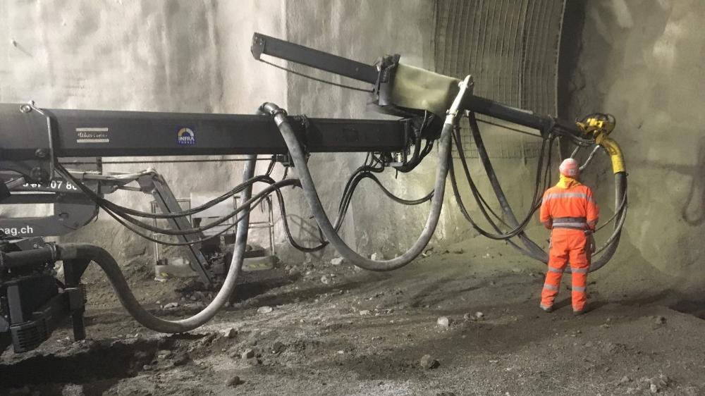 Au cœur du tunnel, on distingue les cintres et treillis, contre lesquels un ouvrier projette du béton.