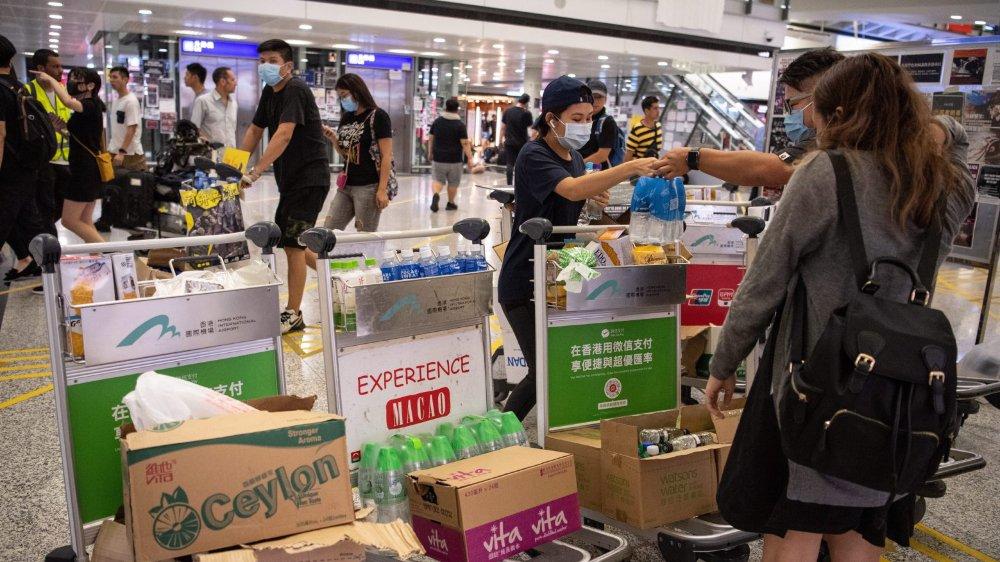Dans le hall de l'aéroport de Hong Kong, des manifestants prodémocratie offrent des boissons aux voyageurs.