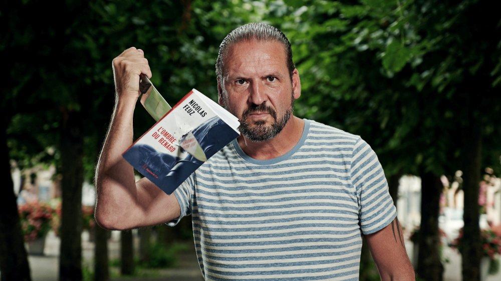 """Un Nicolas Feuz bien affûté pose en terrasse de L'Escarbot, dans le vieux bourg du Landeron, pour la sortie de son nouveau thriller, """"L'ombre du Renard""""."""
