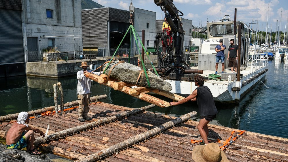 Le menhir en train d'être déposé sur le radeau construit par l'association Pierre à feu, à Hauterive.