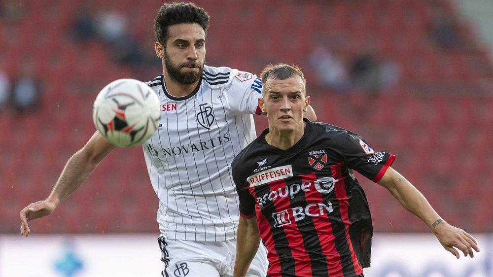 Pour sa première titularisation en Super League, Liridon Mulaj (à droite, à la lutte avec le Bâlois Eray Coemer) n'a pas démérité. (KEYSTONE/Martial Trezzini)