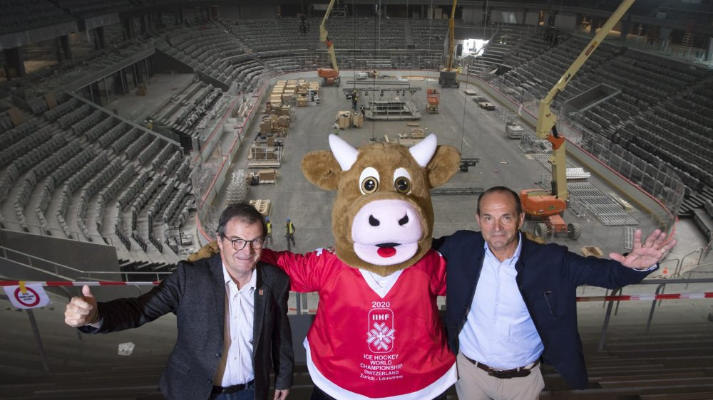 Le président du comité d'organisation Jean-Marie Viaccoz (à gauche) et le secrétaire général Gian Gili entourent Cooly: les Mondiaux 2020 sont sur les bons rails et la nouvelle patinoire de Lausanne sera opérationnelle dans deux semaines.