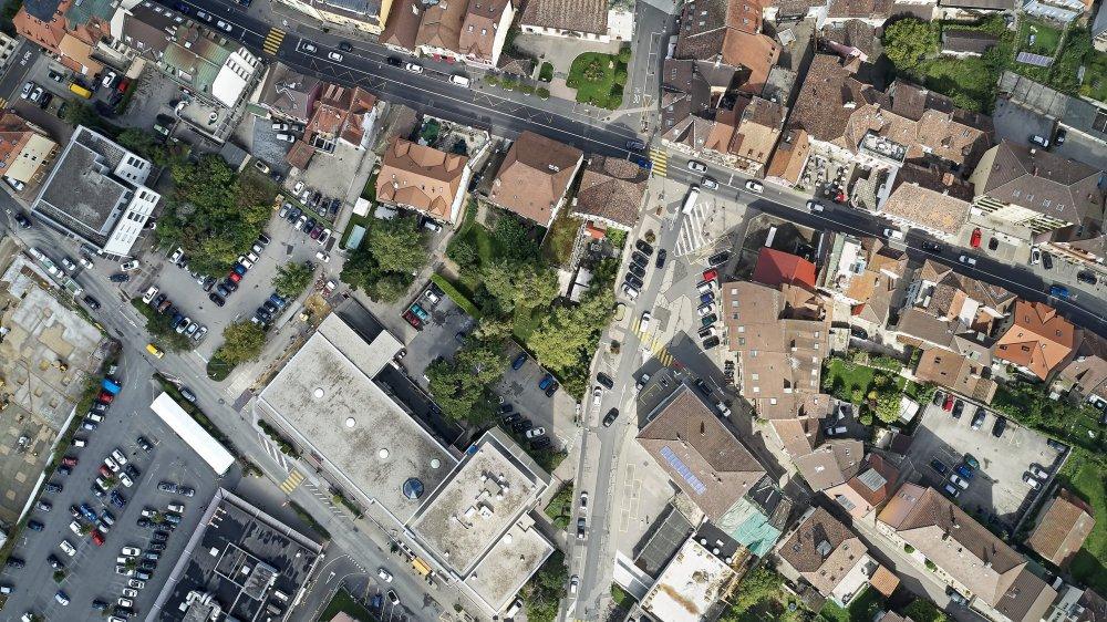 Vue aérienne de Peseux avec, au centre, la place de la Fontaine et au nord, la place du Temple, séparées par la H10. En bas à gauche, la Migros et ses places de parc bordent la rue Jämes-Paris et font face à Cap 2000.