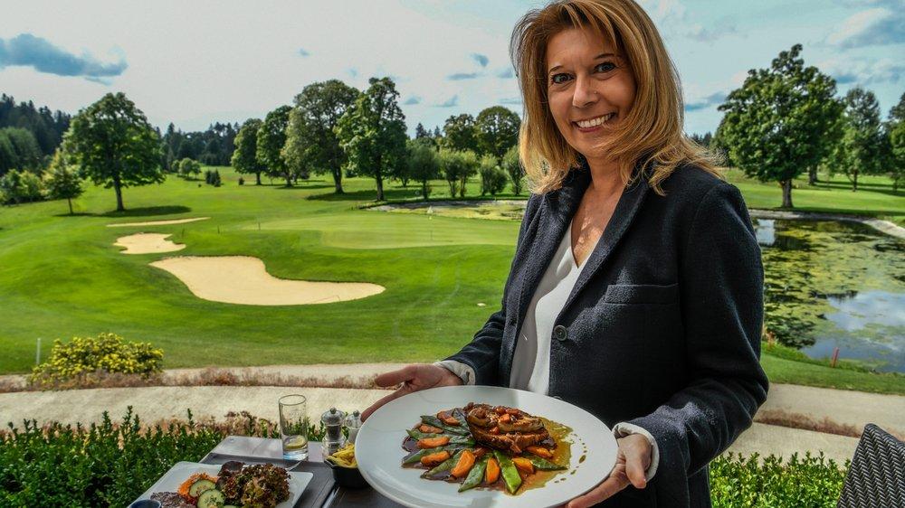 Diana Barbacci Lévy pose avec son plat devant le cadre idyllique du golf des Bois.