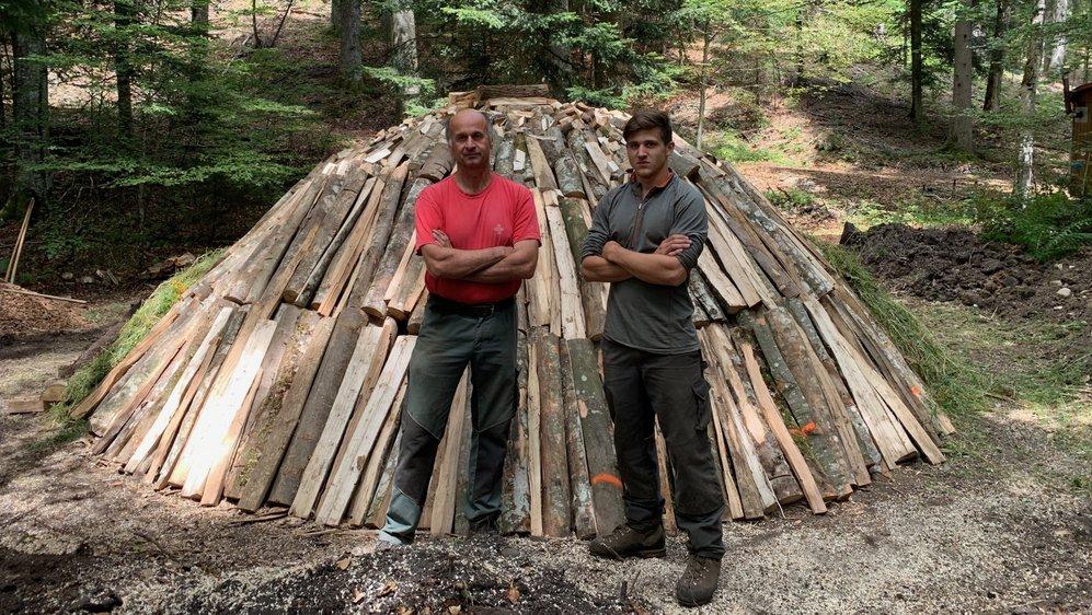 Jean-Pierre Rausis et Maxime Pelet posent fièrement devant leur meule à charbon.