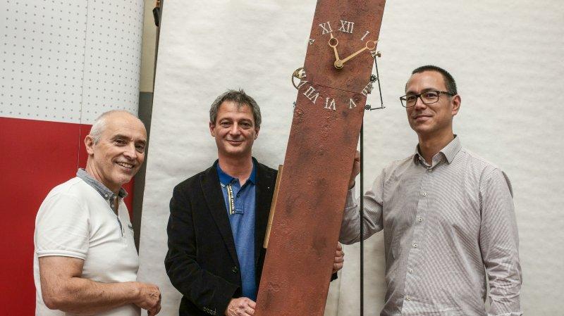 """Les horlogers d'art Michel Bourreau et Fabrice Calderoli (de gauche à droite) présentent la maquette de leur """"Horloge qui penche"""", en compagnie de Thuan Nguyen, directeur du CNIP, qui produira certaines pièces."""
