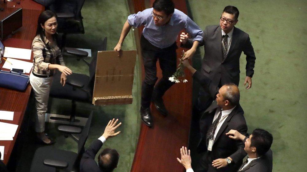 Avant de pouvoir être évacués du parlement par le service de sécurité, des députés hongkongais ont scandé des slogans et brandi des pancartes critiquant l'action de la cheffe de l'exécutif, Carrie Lam.