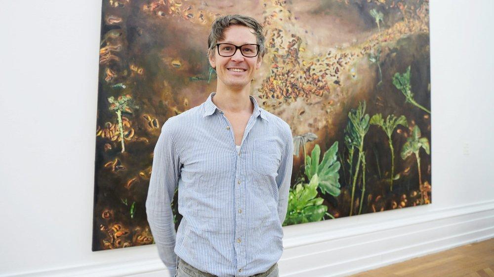 """Léopold Rabus devant un de ses tableaux emblématiques, """"La nuit des affamés"""", montrant une nuée de limaces à l'assaut d'une feuille de salade (2019, huile sur toile, 300 x 400 cm, collection de l'artiste)."""