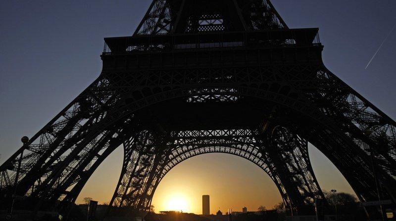 The sun rises behind the Eiffel Tower in Paris, Saturday, Jan. 14, 2012. (AP Photo/Michel Euler)