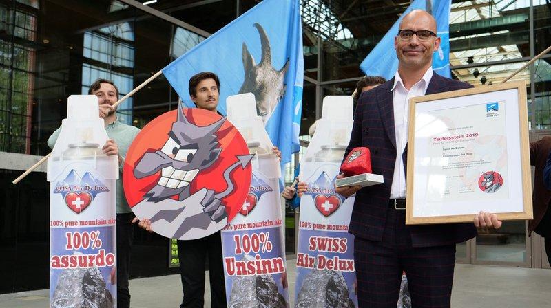 """Markus Klinkmüller (à droite), PDG de Swiss Air Deluxe, s'est vu décerner la """"Pierre du diable"""" pour le bilan carbone désastreux de son air des Alpes en spray."""