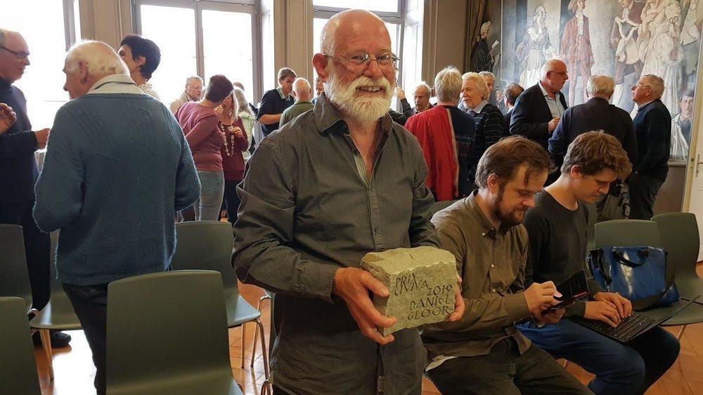 Daniel Gloor portant la pierre symbolique qu'il a apportée à l'édifice du service civil.