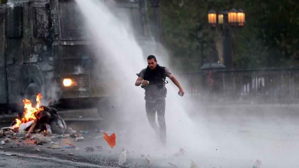 A l'image de ce manifestant, visé par un canon à eau, la contestation restait de mise, ce week-end, au Chili.