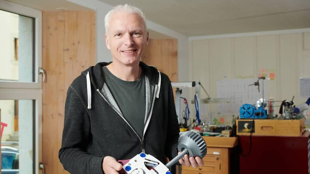 """Roman Winiger, horloger, tient entre ses mains la maquette d'un élément du mouvement """"open source"""" développé par l'association chaux-de-fonnière Open Movement."""