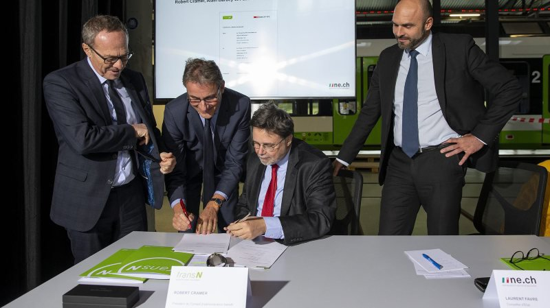 Le directeur Région ouest des CFF, Alain Barbey, le directeur de TransN, Pascal Vuilleumier, et le président du conseil d'administration de TransN, Robert Cramer, signent le contrat de partenariat, sous le regard du conseiller d'Etat Laurent Favre, ce vendredi 22 novembre à Fleurier.