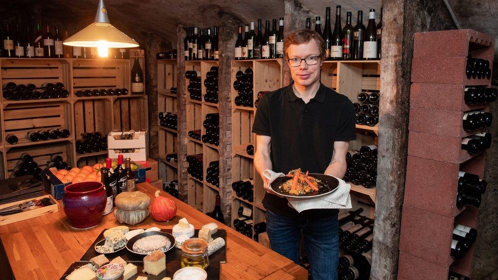 Simon Peguiron présente son plat principal dans la cave à vins et à fromages du restaurant.