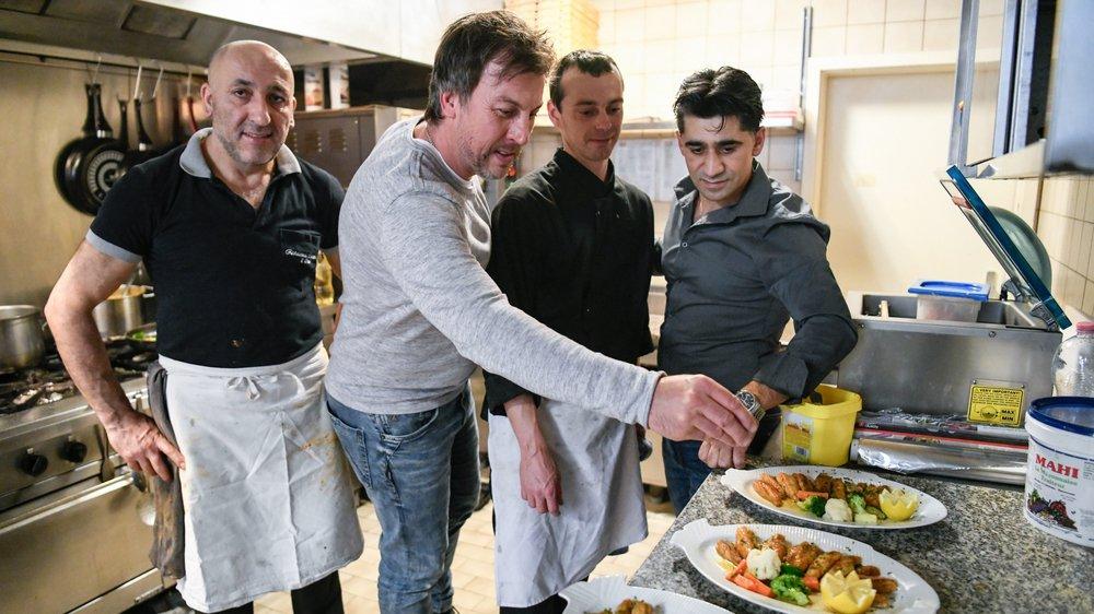 Pour la photo, Philippe Martin (en gris clair) met la dernière main à ses filets de perche en cuisine.