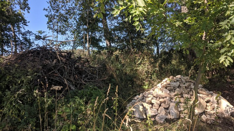 Les tas de bois et tas de pierres, ici sur une exploitation aux Enfers, sont construits avec des matériaux récoltés à proximité des lieux d'installation (pierres issues de l'épierrage des champs, bois issus de coupes de branchages).