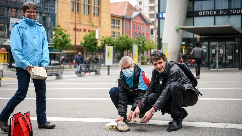 Sur la place Espacité à La Chaux-de-Fonds, les gens, petit à petit, ont amené leur pierre pour alerter sur l'urgence climatique et sociale.