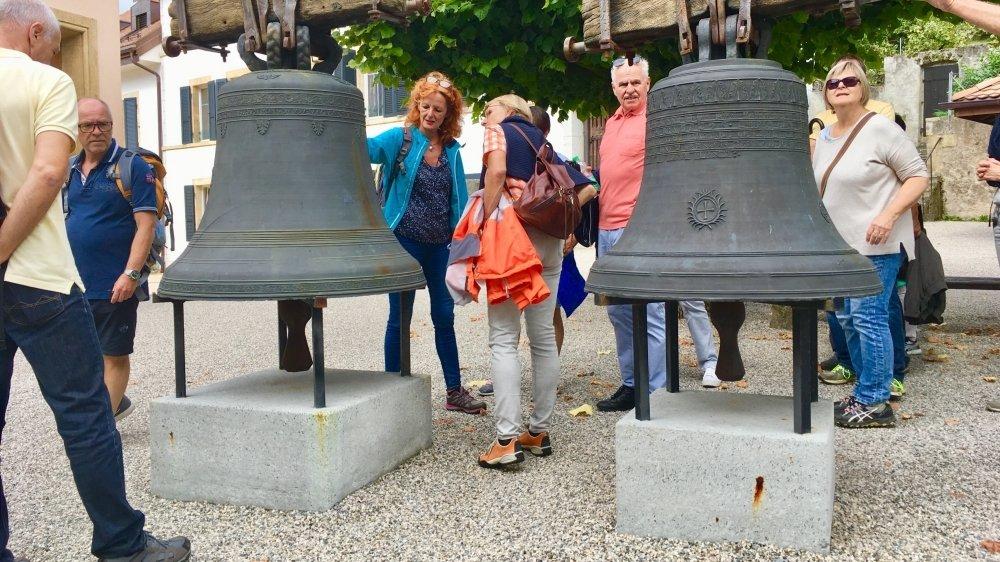 La guide-interprète du patrimoine Monique Chevalley accompagne un groupe de randonneurs vers les cloches de l'église de Saint-Aubin, qui étaient tombées lors de l'incendie du clocher.