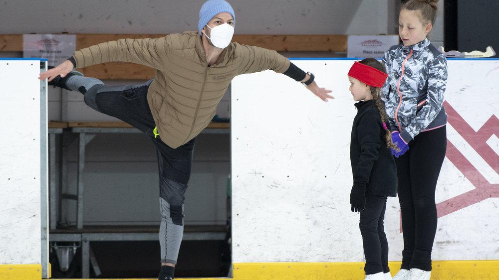 Stéphane Lambiel, avec un masque et un bonnet, montre l'exemple à ses élèves sur la glace, à Champéry.