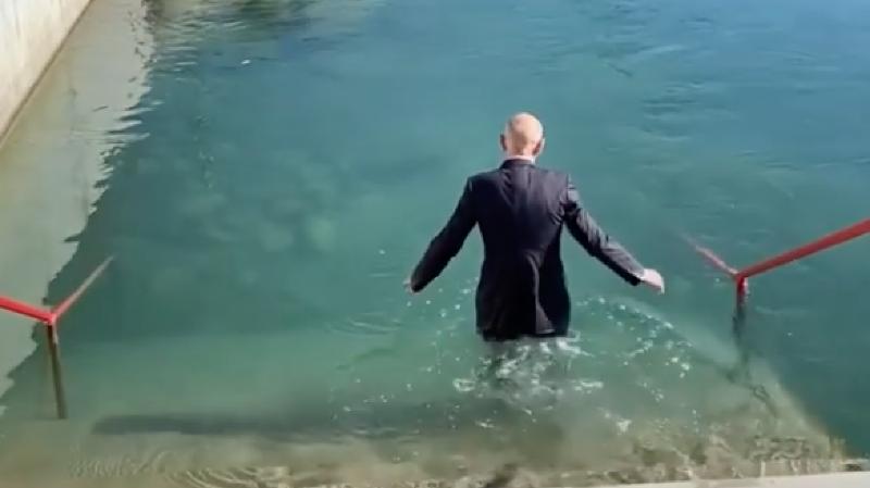 Daniel Koch plonge dans les eaux froides de l'Aar en costume-cravate
