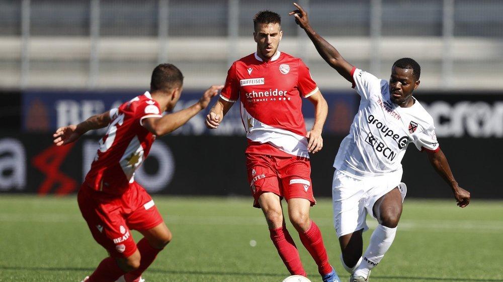 Freddy Mveng (à droite) tente de se battre pour un ballon contre deux joueurs de Thoune (Leonardo Bertone et Simone Rapp): Xamax a souvent été impuissant ce dimanche dans l'Oberland bernois.