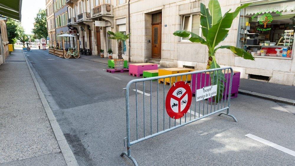 La barrière qui ferme provisoirement la rue de l'Orangerie, une partie du mobilier urbain et, au fond, la terrasse du restaurant Le Bureau.