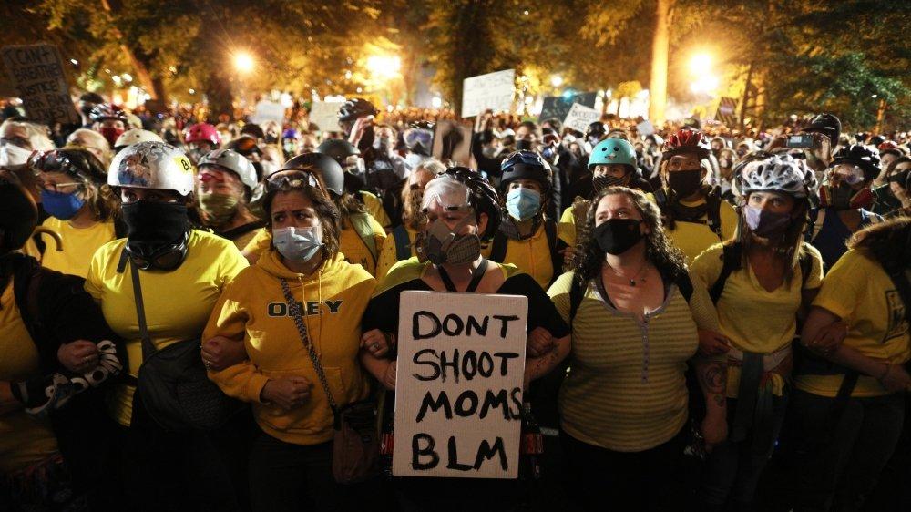 """Le """"mur des mamans"""" forme des chaînes humaines entre les manifestants et les forces de l'ordre."""