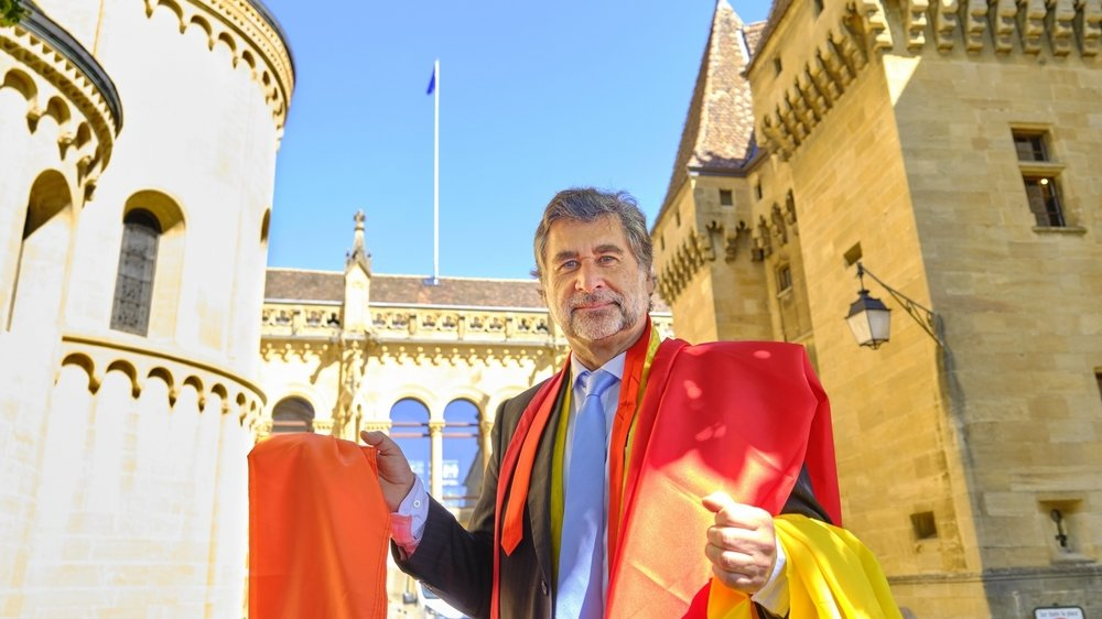 Le médecin cantonal Claude-François Robert avec les drapeaux et ses cravates devant le château où flotte le drapeau bleu.