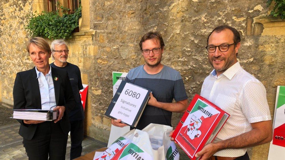 L'huissière du Conseil d'Etat, Véronique Comtesse, reçoit les trois classeurs de signatures de la part des membres du comité d'initiative Christian Piguet, Julien Gressot et Patrick Jobin.