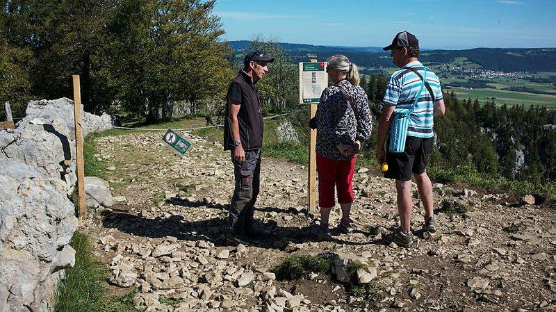 Le ranger Alain Tschanz explique aux promeneurs les mesures interdisant l'accès à la moitié du sentier entre le mur et la falaise.