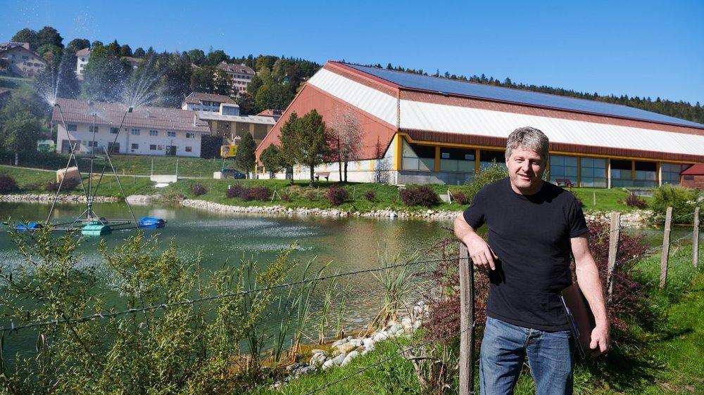 Sylvain Nussbaumer, cheville ouvrière de l'Union sportive des Ponts-de-Martel, pose devant l'étang de refroidissement de la patinoire.