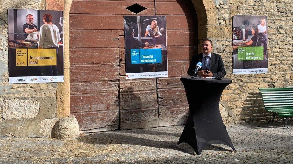 Le conseiller d'Etat Jean-Nat Karakash devant les trois premières affiches de la campagne.