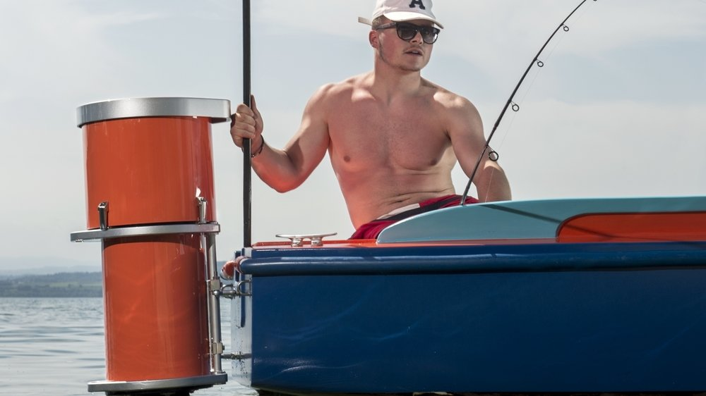 """Un pêcheur amateur pose sur un bateau à côté du moteur Outboard """"Navigaflex"""", sur le lac de Neuchâtel"""